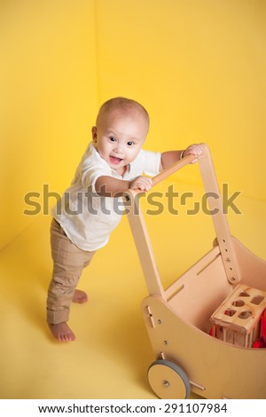 baby holds on to a wooden trolley. asian baby boy standing on yellow background - stock photo
