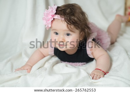 baby in a beautiful dress and a big flower on her head lying on tummy