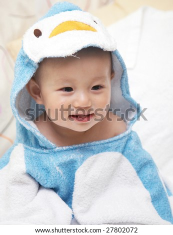 Baby in a cartoon towel after bath. - stock photo