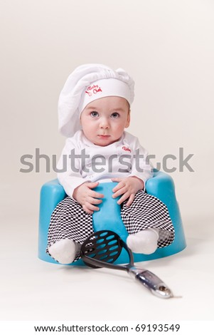 Baby in a chef Outfit Sitting holding cooking utensils