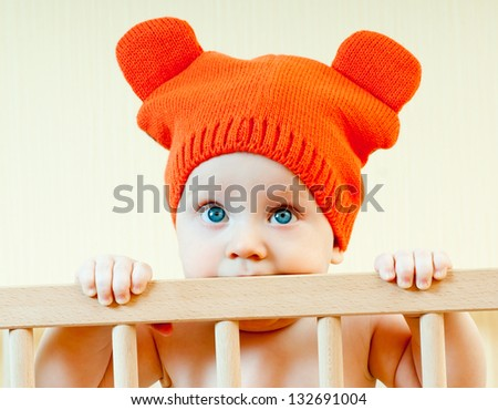 baby in a crib in the cap - stock photo