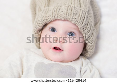 Baby in a huge knitted hat looking surprised - stock photo