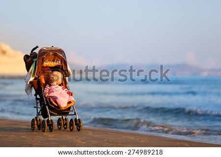 Baby in a stroller on a sandy beach, peacefully looking into infinity and sea waves with great interest, enjoying late summer evening by the sea. Family vacation, traveling with children concept.  - stock photo