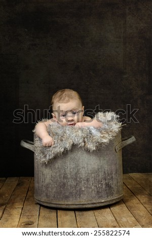 baby in a tin bucket - stock photo