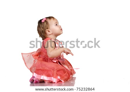 Baby in an elegant pink dress looking something carefully. isolated on white