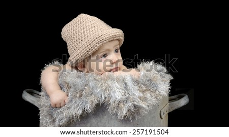 Baby in an old tin tub on black - stock photo