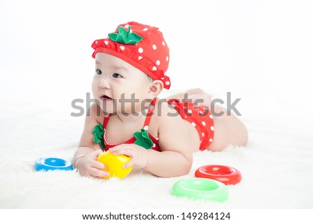 Baby in bikini, hat and sunglasses laying on white blanket  - stock photo