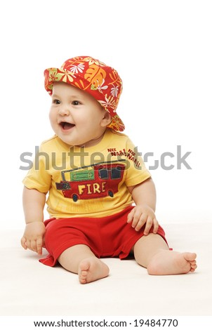 Baby in bright cloths sitting looking sideways laughing