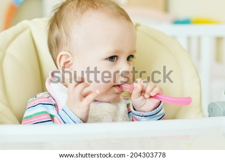 baby in chair  with spoon - stock photo