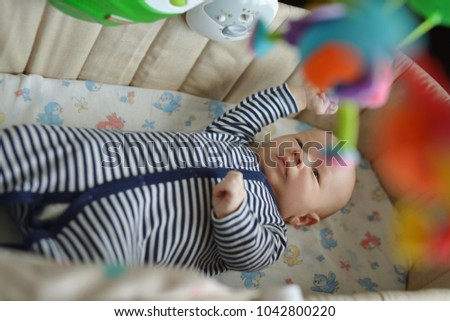 baby in crib looking at the colorful baby mobile