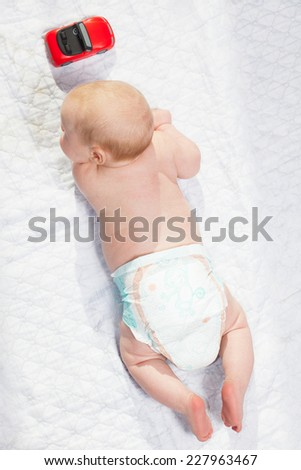 Baby in diaper playing with cars lying on his stomach on top of the form.