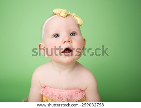 Baby in Easter outfit and headband looking up, infant baby girl - stock photo