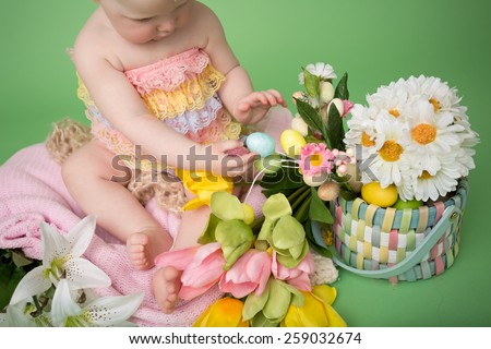 Baby in Easter outfit, holding Easter eggs, tulip flowers on pink blanket - stock photo