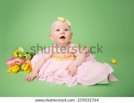 Baby in Easter outfit on her tummy, easter egg and flowers - stock photo