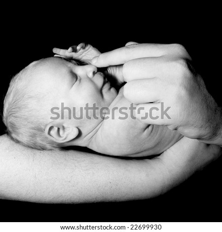 baby in father's hands over black