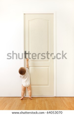 Baby in front of a closed door, trying to reach the handle - stock photo