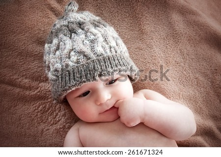 baby in hat on brown fur background - stock photo