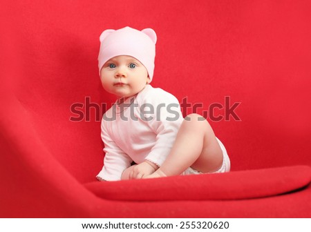 Baby in hat sitting on the red armchair at home
