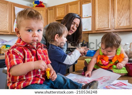 Baby in kitchen with guilty face looks at camera - stock photo