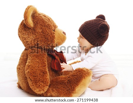 Baby in knitted brown hat playing with big teddy bear - stock photo
