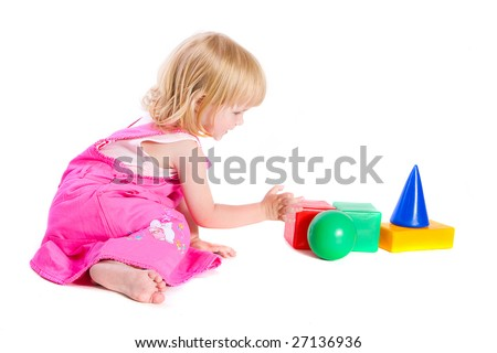 Baby in pink dress playing with bright blocks - stock photo