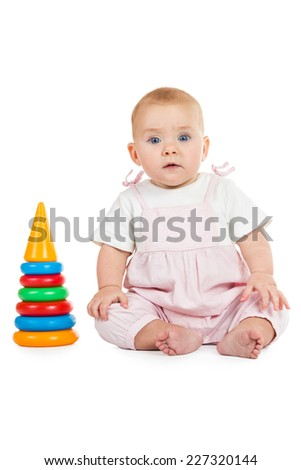 Baby in pink jumpsuit sits next to a toy pyramid isolated on white background