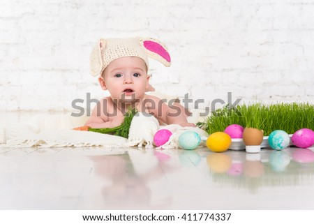 Baby in rabbit costume and Easter eggs. Fresh grass