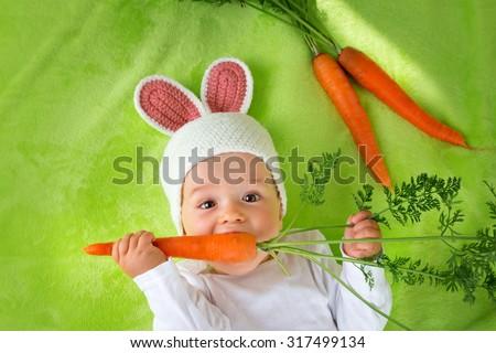 Baby in rabbit hat eating fresh carrot - stock photo