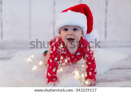 baby in red with cap playing with led lights