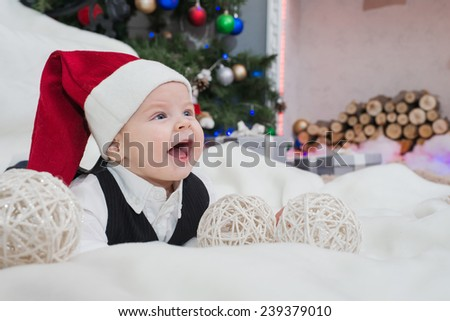 Baby in Santa Claus hat lying on the carpet. Christmas tree in the background - stock photo