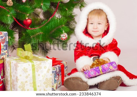 Baby in Santa costume at the Christmas tree with gifts - stock photo