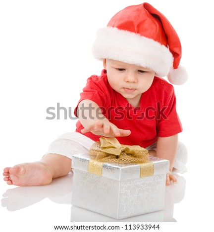 Baby in Santa hat playing with Christmas gift box. isolated on white background - stock photo