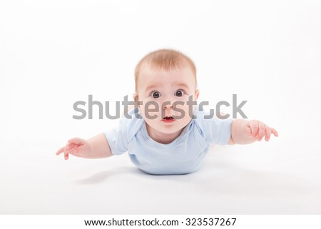 baby in the body lying on his stomach on a white background and looking at the camera, picture with depth of field