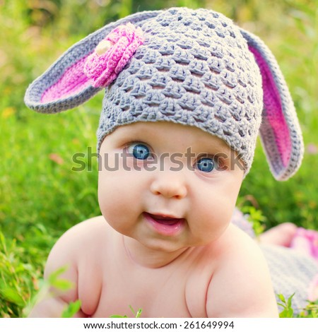 Baby in the hat like easter bunny or lamb of green grass, closeup face. - stock photo