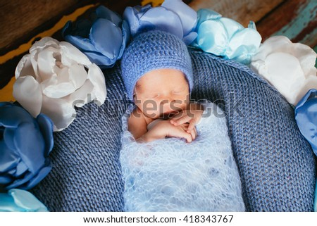 Baby in the knitted hat on the blue bed
