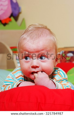 Baby in the nursery playing on the pillow