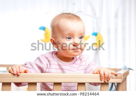 Baby in the playpen looks serious and concentrated