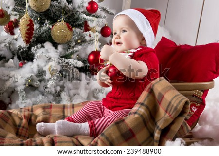 Baby in the Santa Claus hat holding a red ball - stock photo
