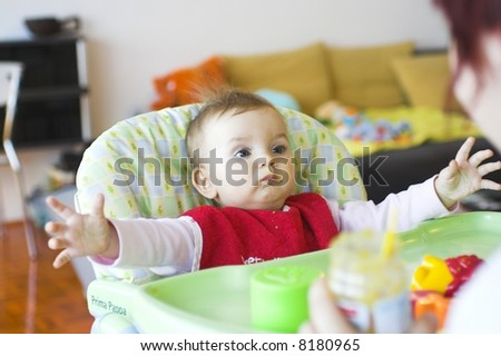 Baby in toddler seat - arms prepared to hug  mum - stock photo