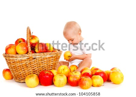 Baby in white bodysuit playing with apples - stock photo
