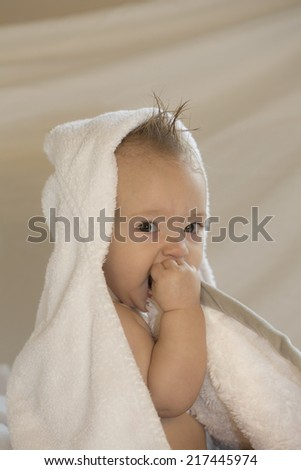baby in white hooded towel holding blanket to face - stock photo