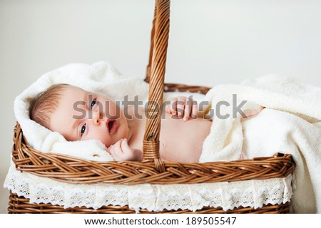 Baby in wicker basket. Little baby lying in wicker basket and covered with towel
