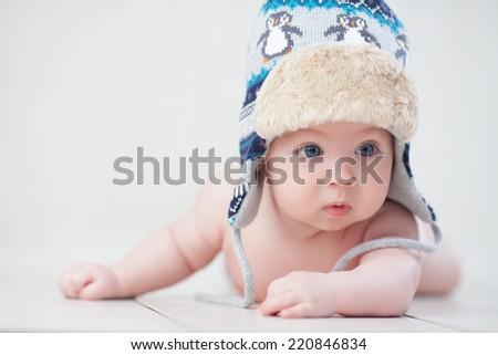 Baby in winter hat lying on the floor - stock photo
