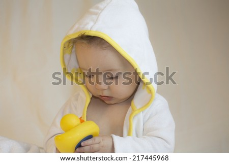 baby in yellow and white bathrobe playing with rubber duck