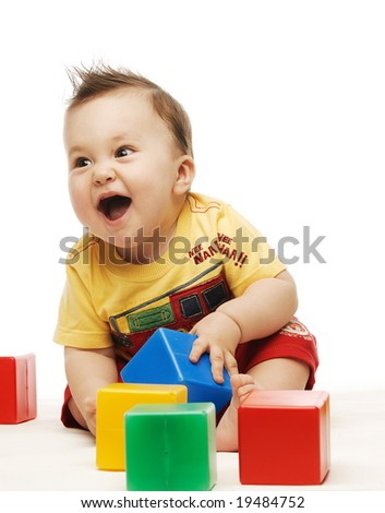 Baby in yellow shirt playing with bright colorful blocks - stock photo