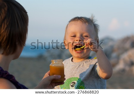 baby is feeding baby food, with green plastic spoon, by the sea, on sand beach, beach with rocks. Mother is feeding a baby. Healthy food. - stock photo