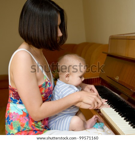 Baby is learning to play the piano at his mother's lap - stock photo
