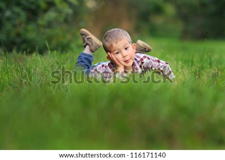 baby is lying in the grass and looking thoughtfully - stock photo