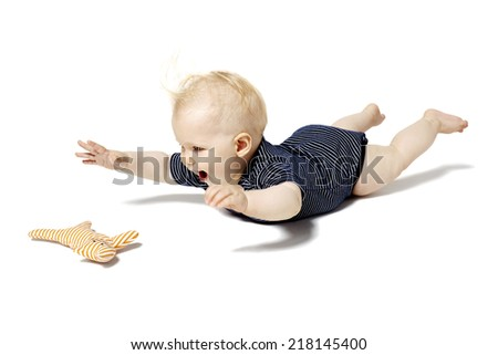 Baby is lying on a belly and playing with cat toy. - stock photo