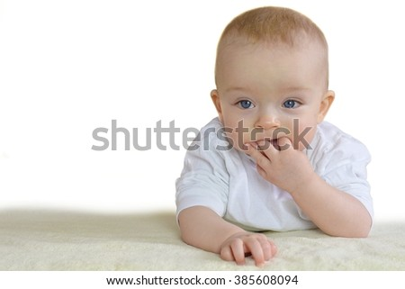 Baby is sucking fingers because of his first teeth - stock photo